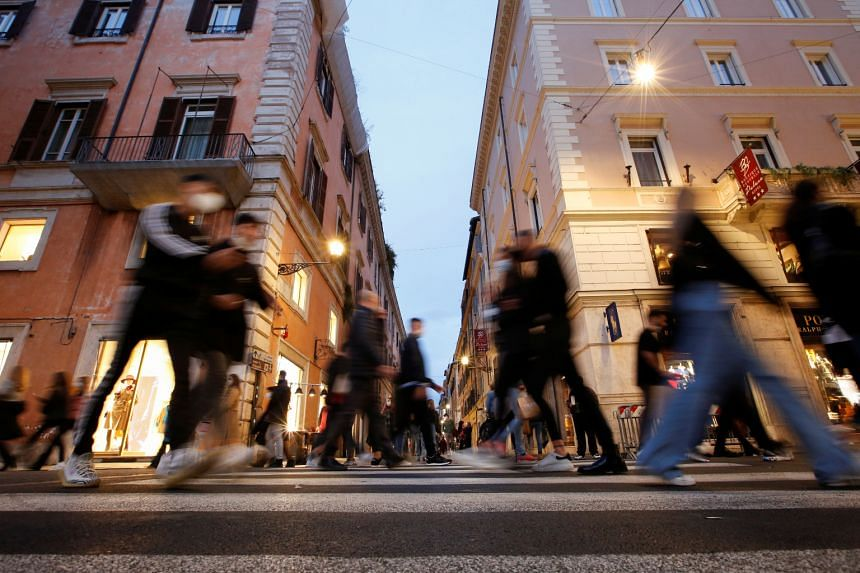 People walk along the shopping street of Via del Corso in Rome, on Nov 14, 2020.