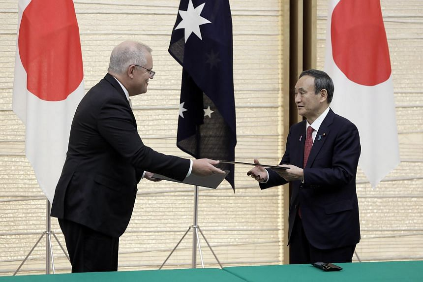 Japanese Prime Minister Yoshihide Suga (right) and Australian counterpart Scott Morrison exchanging documents in Tokyo on Nov 17, 2020.