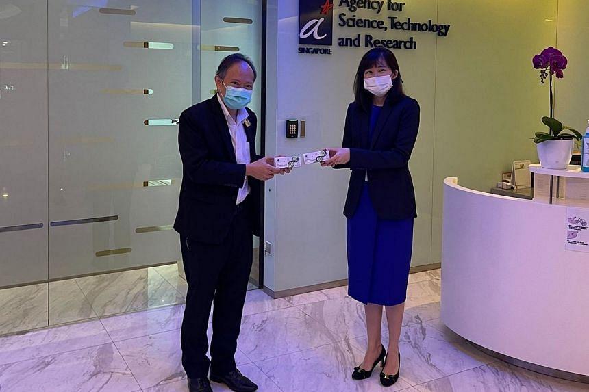 Ambassador of Thailand Suriya Chindawongse symbolically handing over 10,000 covid-19 tests to A*Star's director of biomedical research council Amanda Ang.
