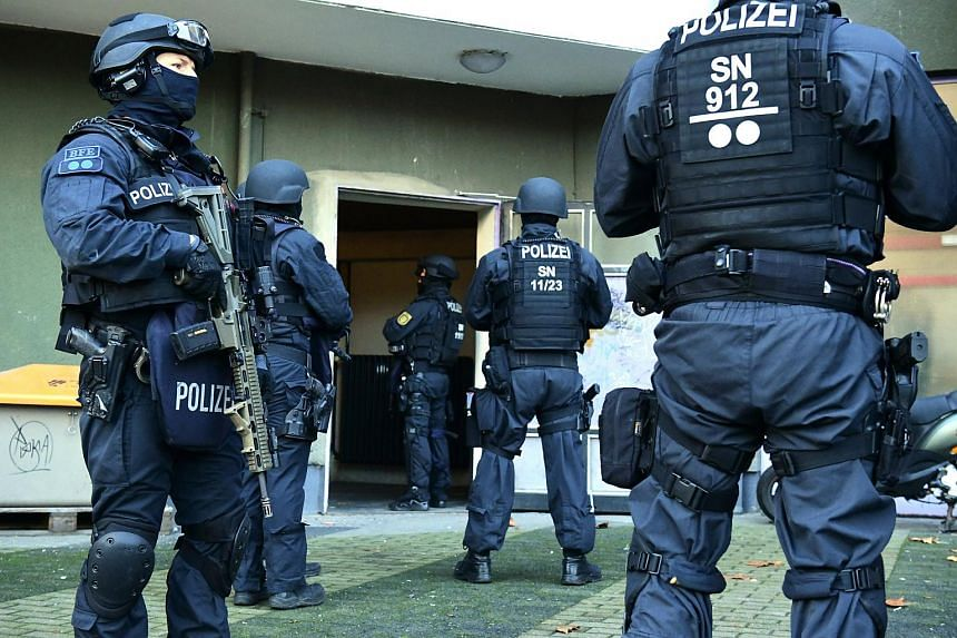 Armed police officers standing guard at the site of a raid in connection with the Dresden heist, in Berlin, Germany, on Nov 17, 2020.