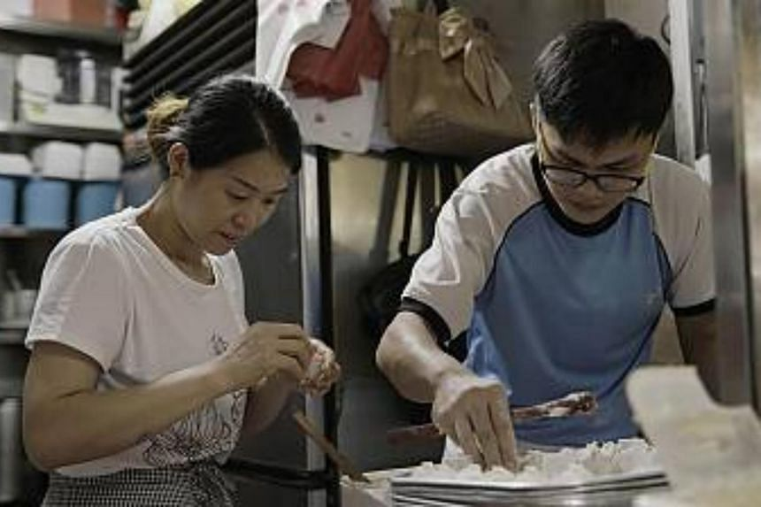 A mother shares the skill of making dumplings with her son at her hawker stall.