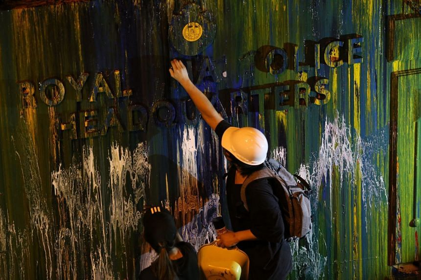 Pro-democracy protesters try to remove lettering from the front gate at the Royal Thai police headquarters.