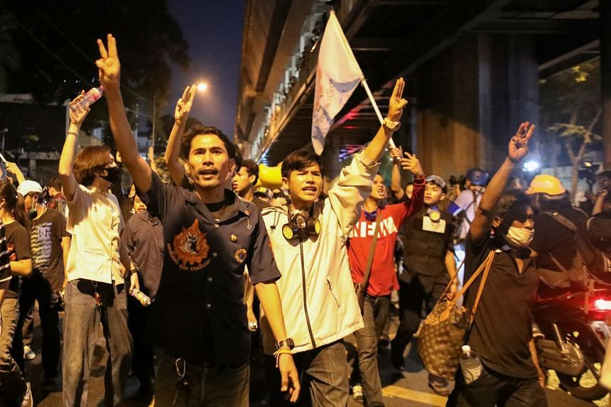 Demonstrators show the three-fingered salute during a rally in Bangkok.