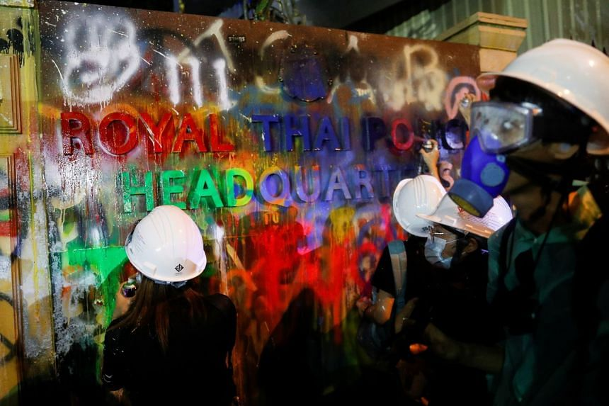 Demonstrators spray-paint a plaque in front of the police headquarters in Bangkok.