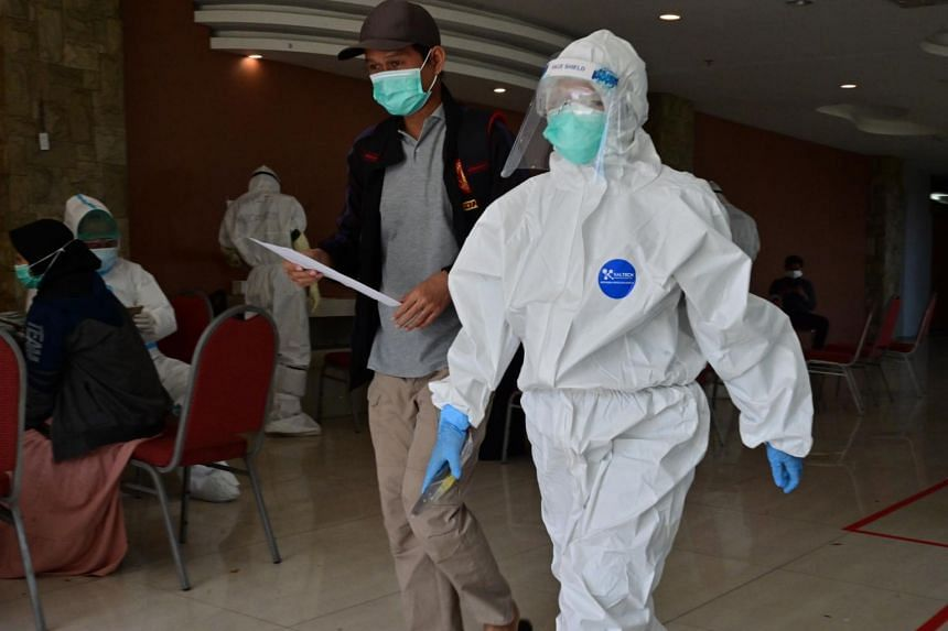A nurse wearing personal protective equipment (PPE) picks up a recovered coronavirus patient at a hotel in Karawaci, Indonesia's Banten province on Oct 5, 2020.