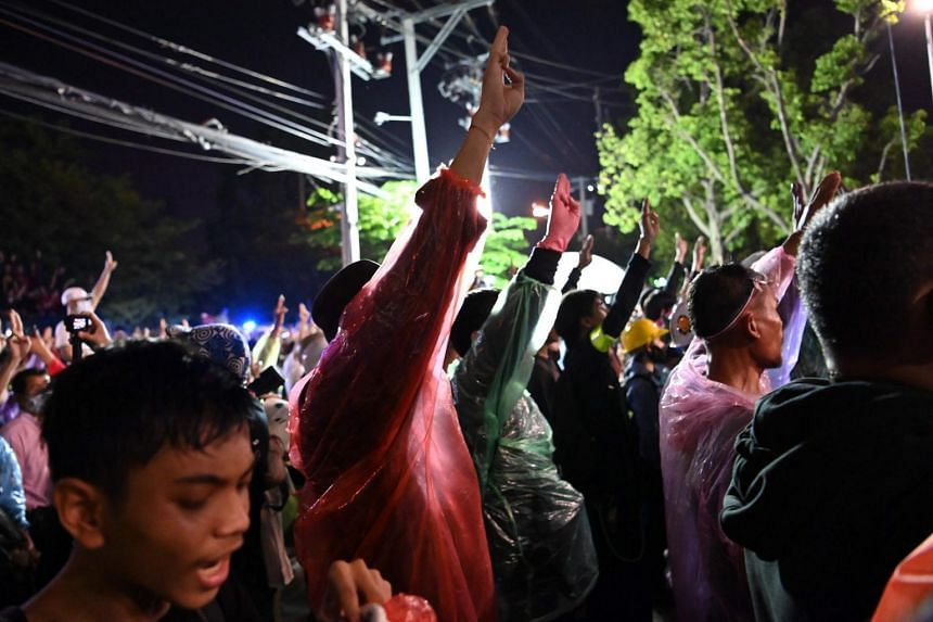 Pro-democracy protesters hold up the three-finger salute during an anti-government rally in Bangkok on Nov 17, 2020.