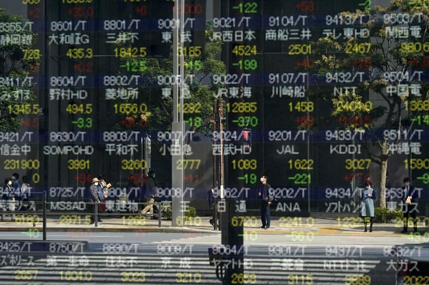 Passersby are reflected in a stock market indicator board in Tokyo on Nov 9, 2020.