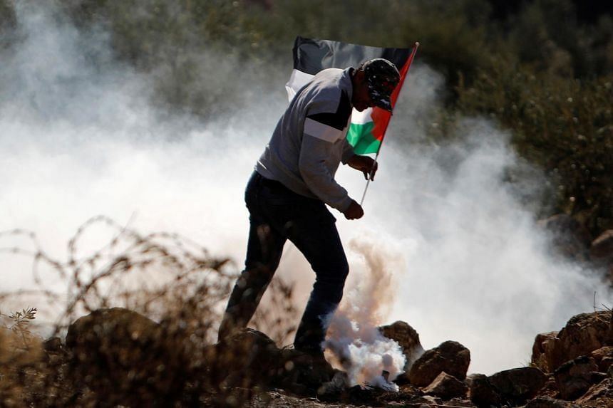 A demonstrator holds a Palestinian flag during a protest in the Israeli-occupied West Bank on Nov 13, 2020.