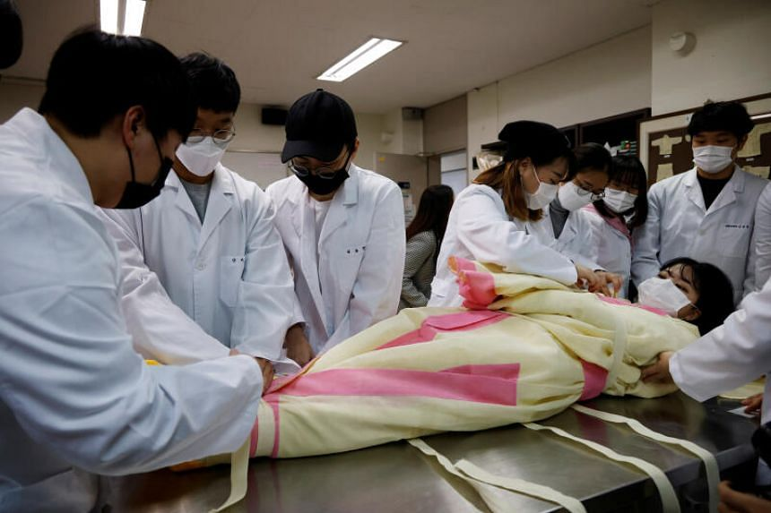 Ms Park Se-jung is laid down for practice on how to shroud the dead during a class in Seongnam, South Korea, on Nov 2, 2020.