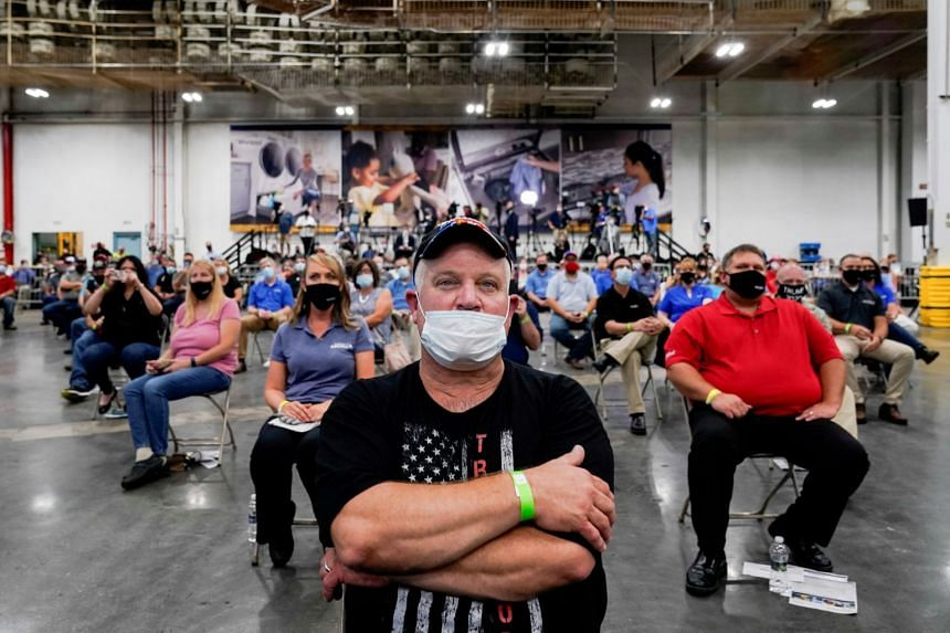 Workers listen to US President Donald Trump as he speaks at a washing machine factory in Clyde, Ohio.