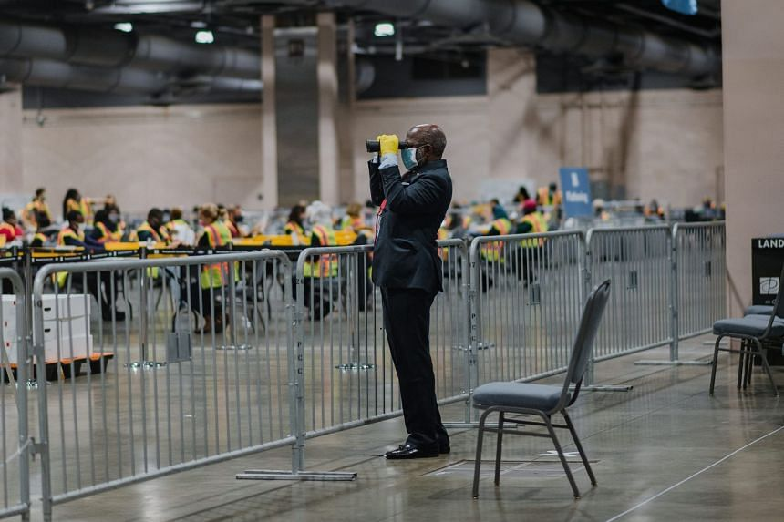 An official poll watcher uses binoculars as workers count ballots in Philadelphia, Pennsylvania, on Nov 3, 2020.
