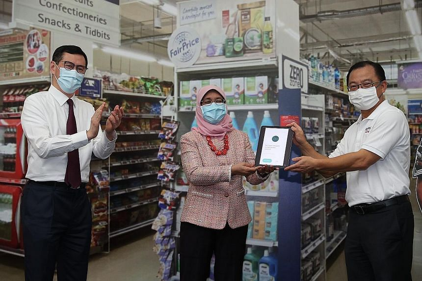 President Halimah Yacob made the first donation of $40 to The Boys' Brigade Share-a-Gift (BBSG) charity drive by scanning a QR code using a bank app yesterday. With her at the opening ceremony at BB Campus in Ganges Avenue are Prudential Singapore's