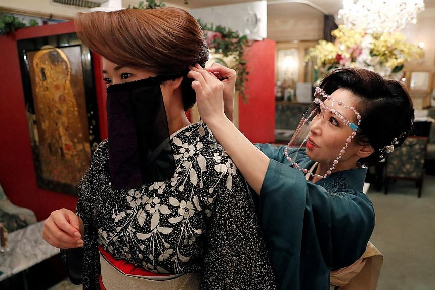 "A bar hostess helping another to wear a ""face veil mask"" at a club in Tokyo on Monday. Japanese kimono maker Otoduki, which invented the mask, said it was inspired by the cloth masks worn by belly dancers, and it helps hostesses, dancers and musician"