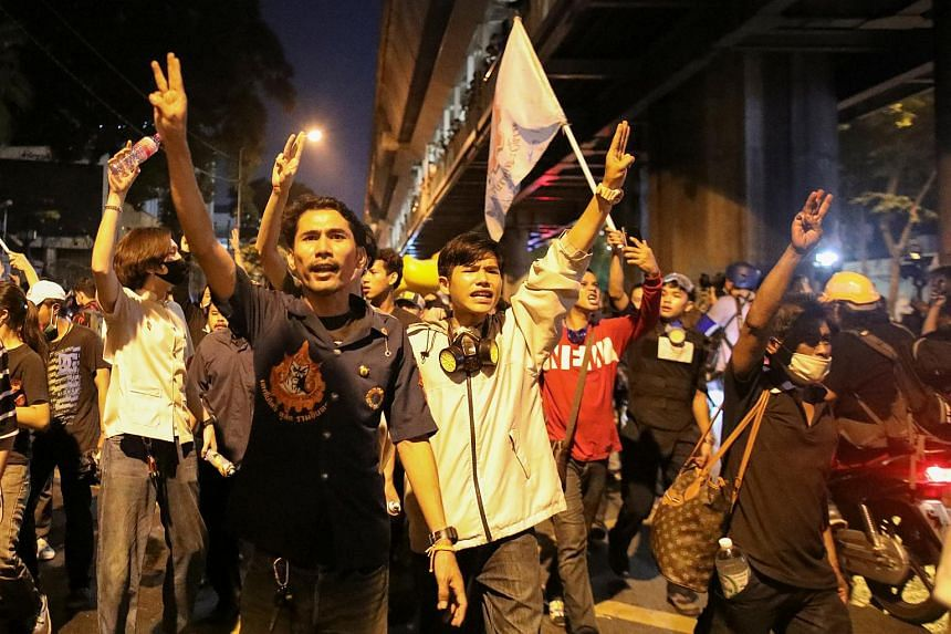 Demonstrators show the three-fingered salute during a rally in Bangkok, on Nov 18, 2020.