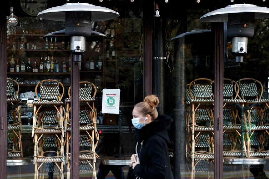 A woman walks past a closed restaurant in Paris during lockdown, on Nov 18, 2020.