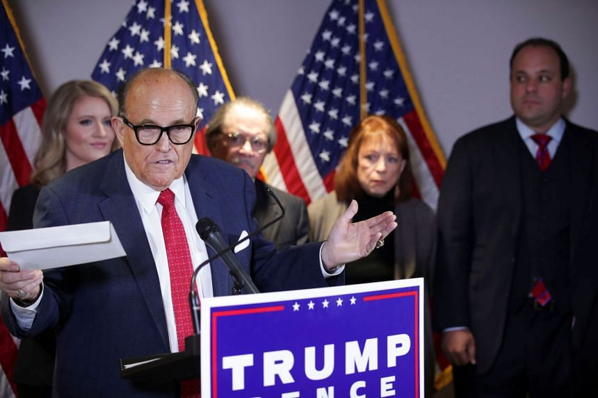 Rudy Giuliani holds up what he identified as a replica mail-in ballot during a  news conference in Washington, Nov 19, 2020.