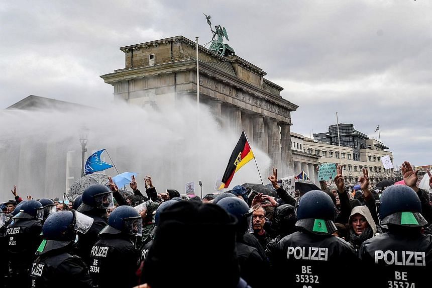 Riot police using a water cannon to break up a demonstration against Germany's coronavirus restrictions, near Berlin's Brandenburg Gate, on Wednesday. Two weeks into a partial shutdown, contagion rates in the country are still nearly triple the level