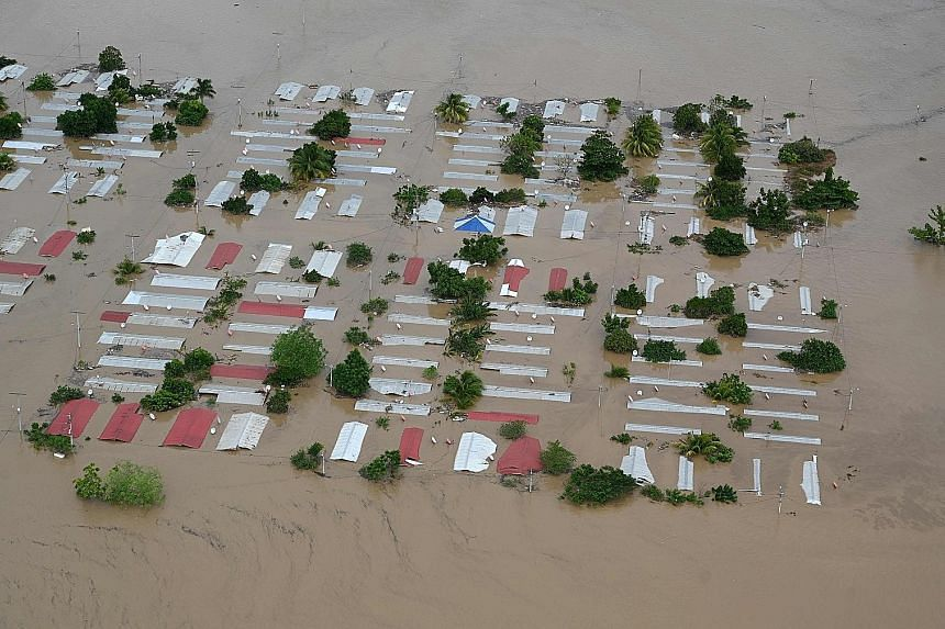 HONDURAS Above: An area around San Pedro Sula flooded by the overflowing Chamelecon river after the passage of Iota on Wednesday. NICARAGUA Far left: A photo from Catholic Relief Services showing a man standing in a house damaged by Iota in Puerto Ca