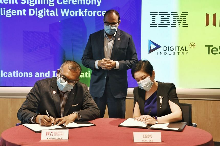 Minister for Communications and Information S Iswaran (centre) witnessing the signing of the MOI between IBM's Ms Lee Hui Li and IMDA assistant chief executive Kiren Kumar on Nov 20, 2020.