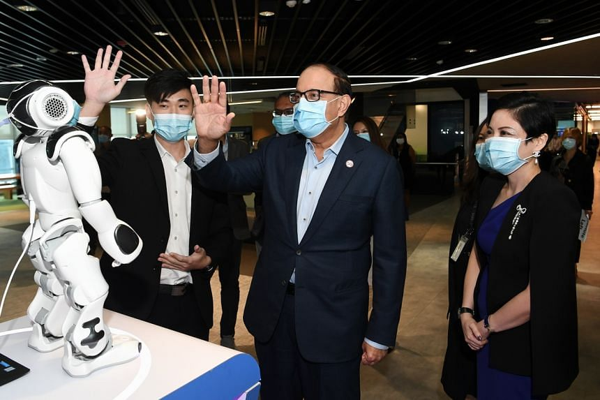 Minister for Communications and Information S Iswaran interacting with NAO, a robot that recognises hand gestures, at IBM on Nov 20, 2020.