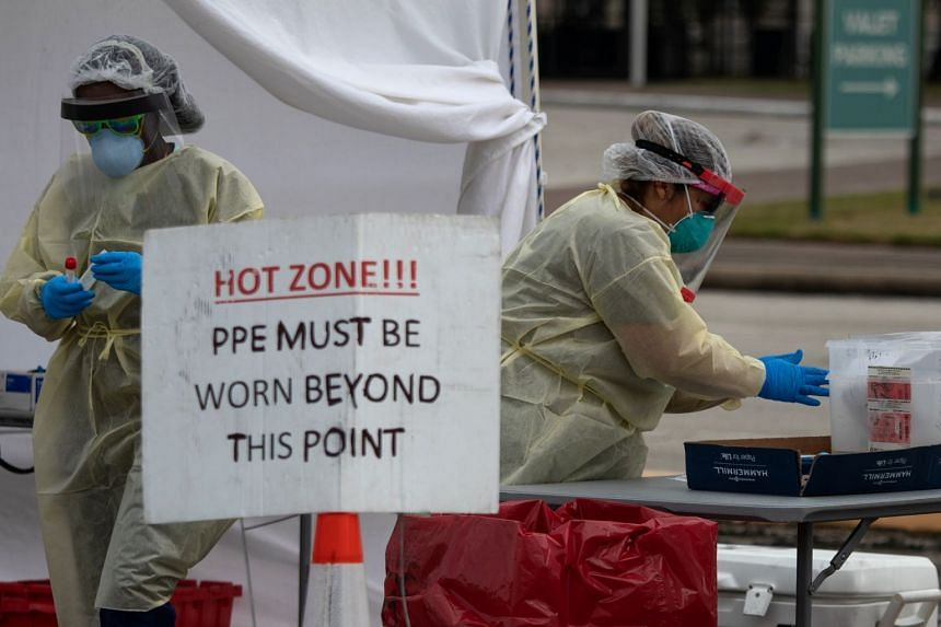 Healthcare workers prepare specimen collection tubes at a coronavirus drive-thru testing location in Houston, Texas.
