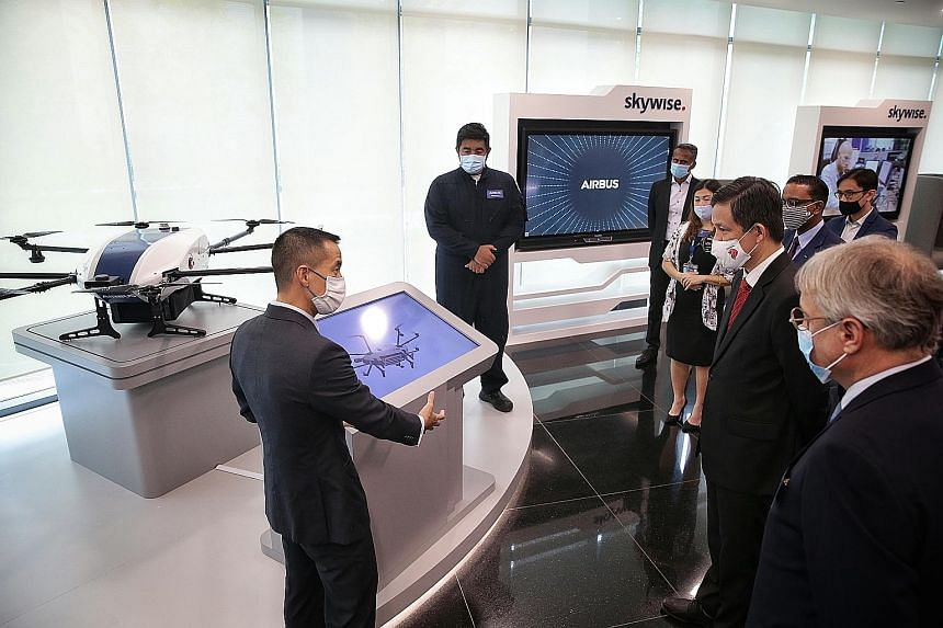 Trade and Industry Minister Chan Chun Sing being given a tour of the Airbus Singapore Campus' Digital Experience Centre yesterday, accompanied by Airbus chief commercial officer and head of international Christian Scherer (right). The campus consolid