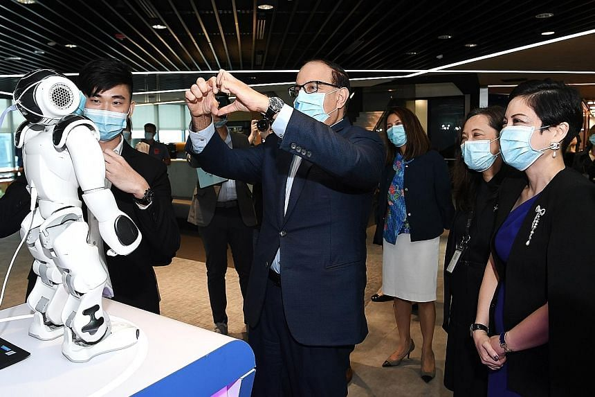 Communications and Information Minister S Iswaran making a gesture to Nao, a humanoid robot which can recognise hand gestures, during his visit to IBM yesterday. He was at the tech firm to witness the signing of the memorandum of intent between IBM a