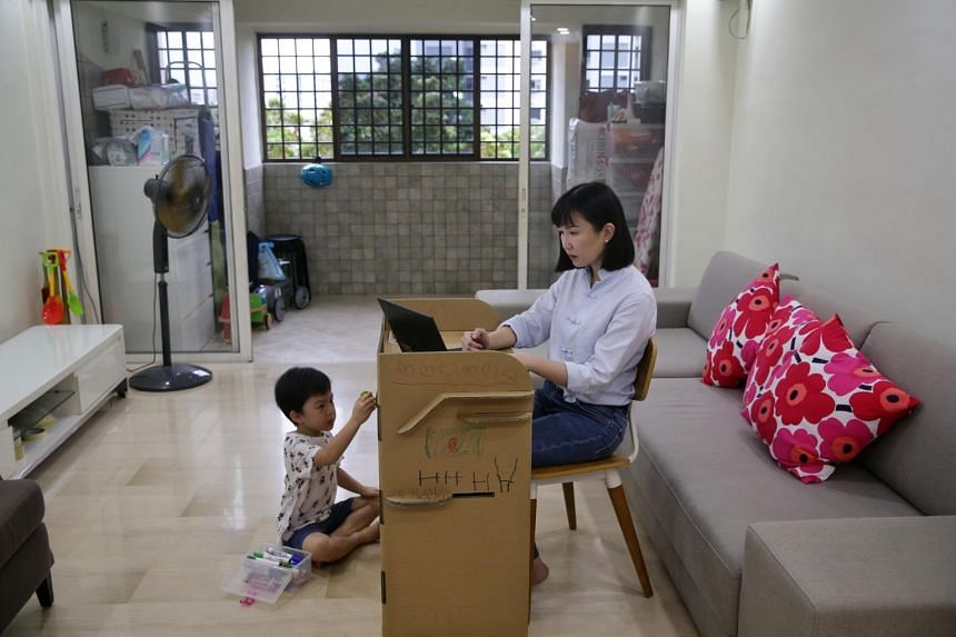 Ms Gigi Su working from home as her son Zachary Wu, five, doodles on her cardboard work desk on Nov 20, 2020.