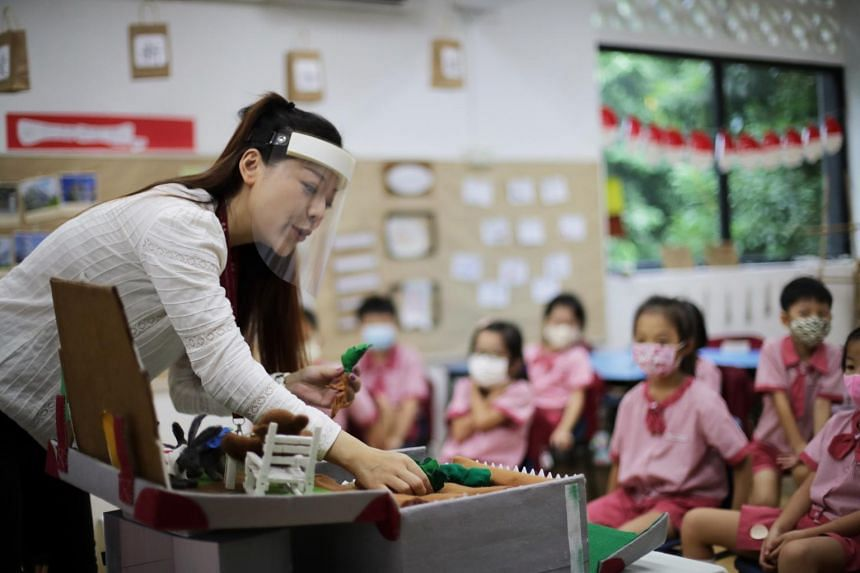 Madam Zhang Xuan Hong, a Chinese language teacher engage the K2 preschoolers using the teaching aid.