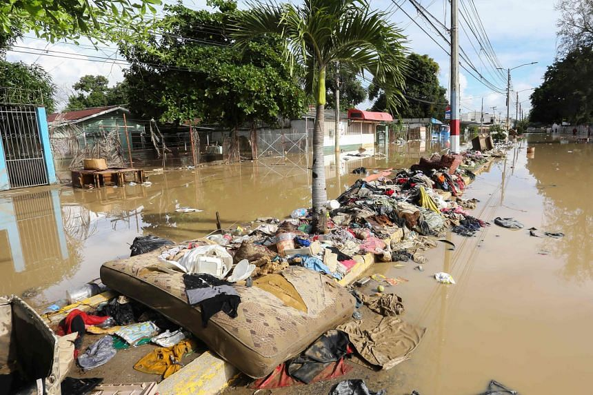 Clothes, a mattress and furniture washed up between two flooded streets in the municipality of La Lima in Honduras yesterday, after heavy rain from Hurricane Iota caused the Chamelecon River to overflow. The number of reported deaths on Thursday rose