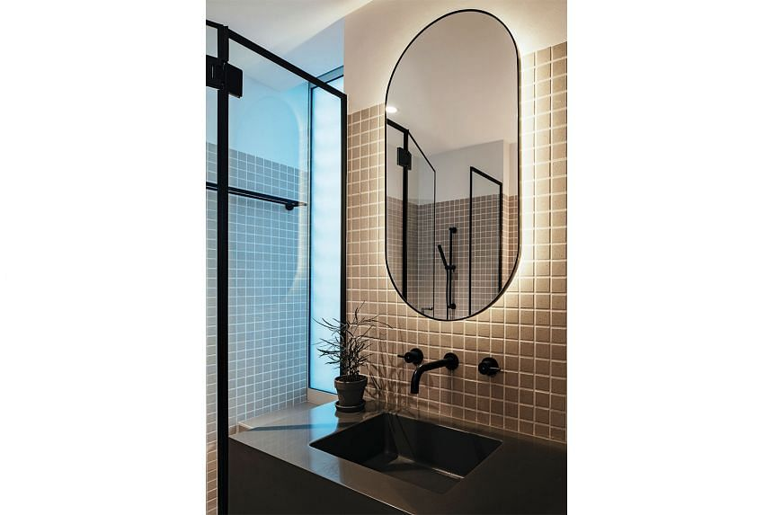 The monotony of angular shapes in the bathroom is broken by a backlit oval mirror (above).
