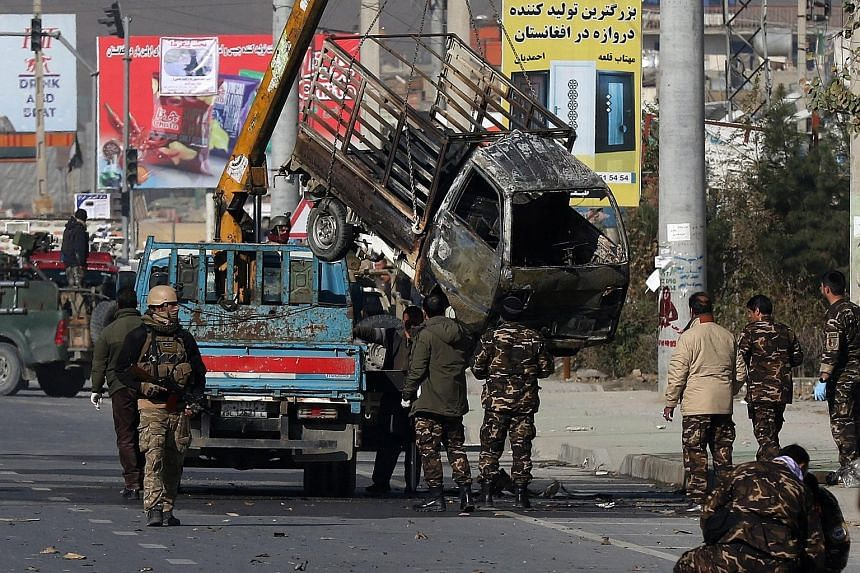 Security personnel inspecting a damaged vehicle after the attack in Kabul yesterday. The explosions, which took place close to the diplomatic enclave, sent warning sirens blaring from embassies and came two days before a major donor conference for Af