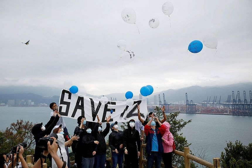 The protesters releasing balloons with the names of the 12 detainees yesterday on Hong Kong's Kat O island, overlooking the area where the Chinese prison is located. The 12 were caught on Aug 23 trying to flee the city by boat. PHOTO: REUTERS