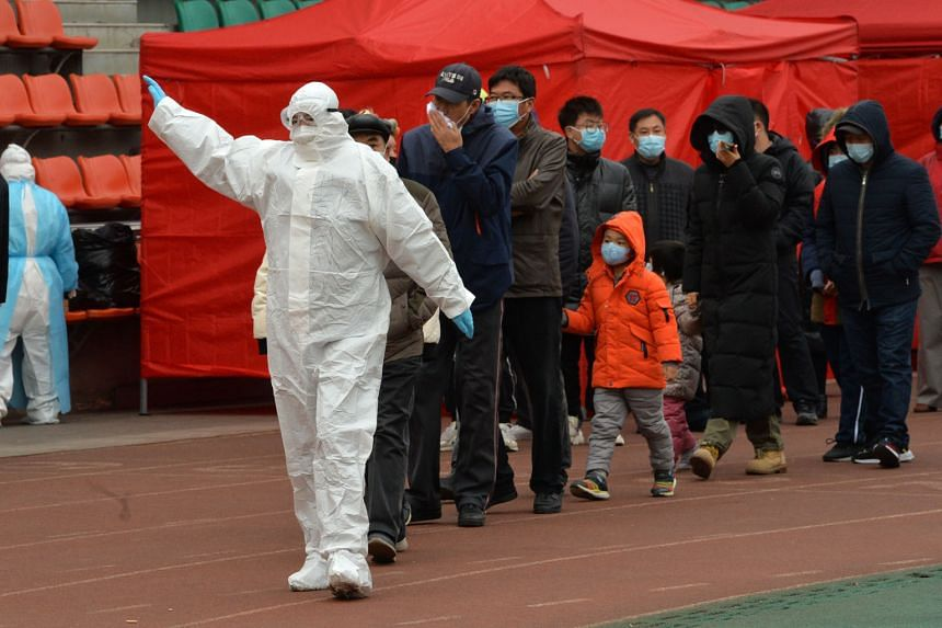 A Chinese government worker leading a group of citizens to take swab samples for the Covid-19 test in Tianjin yesterday, under a three-day screening programme for nearly three million of its residents.