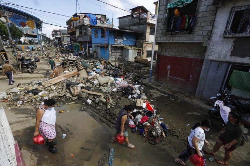 People walk past trash and debris in a street at a riverside community in Marikina City, Metro Manila, on Nov 18, 2020.