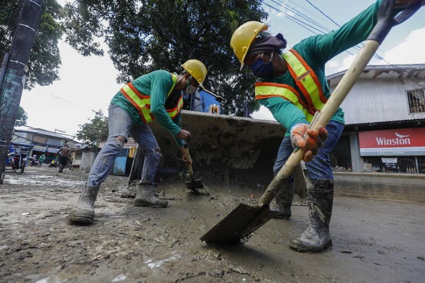 Workers clean up muddied roads at a flood-affected community in Marikina City, Metro Manila, on Nov 16, 2020.