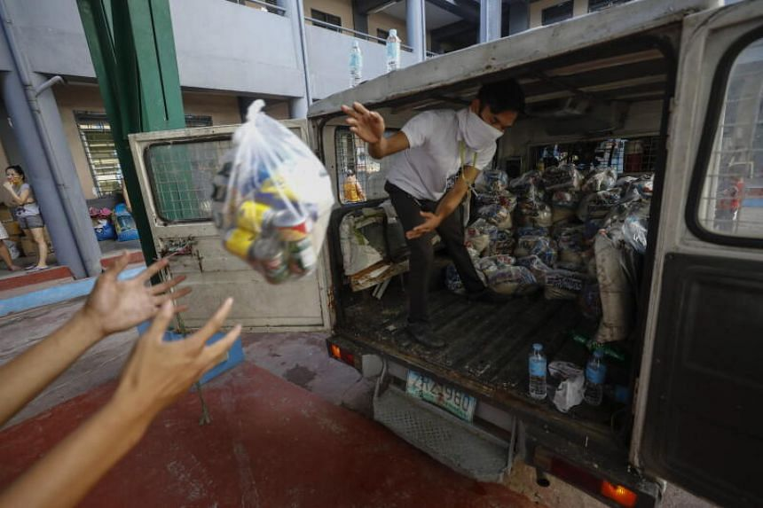 Workers unload relief goods from a van at an evacuation centre in Marikina City, Metro Manila, on Nov 16, 2020.