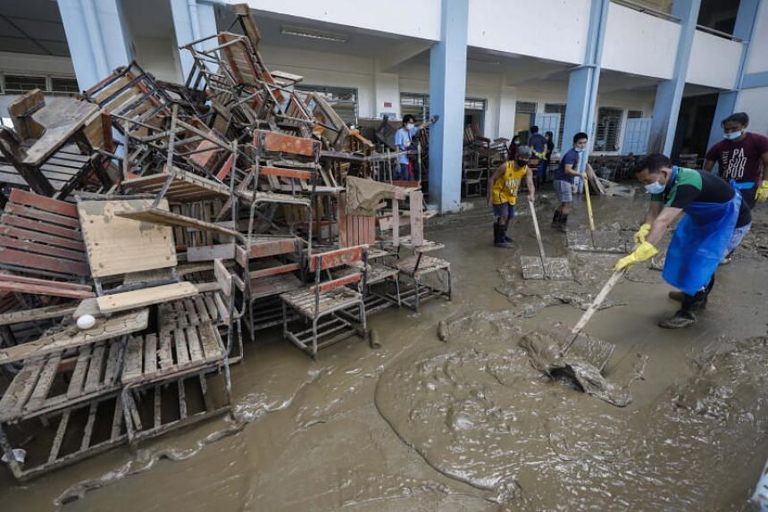 Residents and staff clean a muddied school at a riverside community in Marikina City, Metro Manila, on Nov 18, 2020.