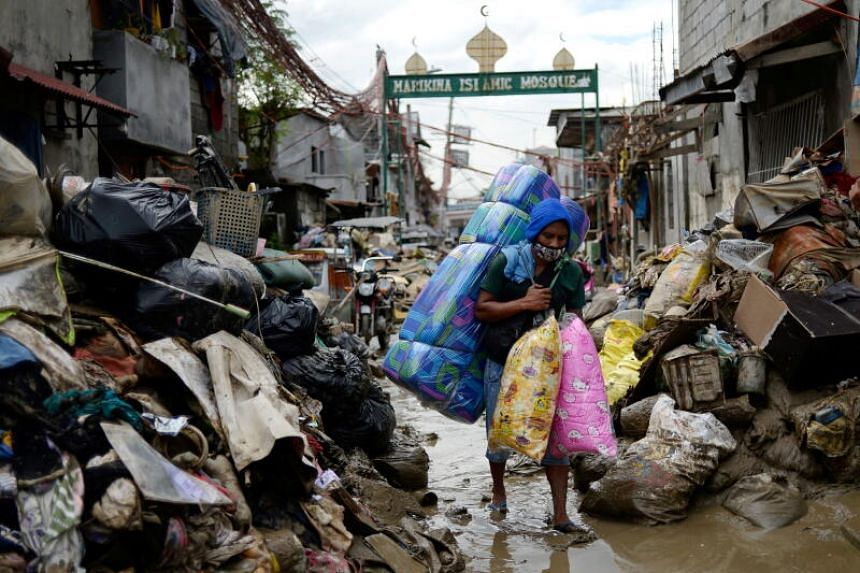 A man selling pillows and mattresses walks past debris from the flood brought by Typhoon Vamco, in Marikina, Metro Manila, on Nov 16, 2020.