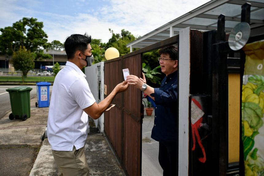 Minister of State for Sustainability and the Environment Desmond Tan giving the new Dengue Prevention Toolkit to Mr Justin Leong at Jalan Chempaka Puteh on Nov 22, 2020.