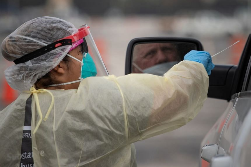 A healthcare worker uses a swab to test a man at a drive-thru coronavirus testing location in Houston, Texas.