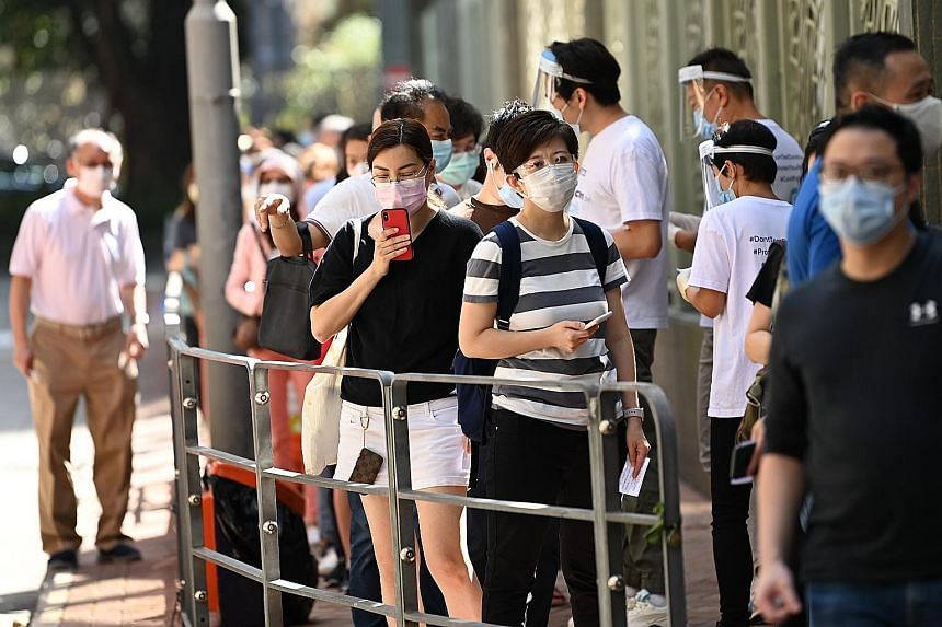 People queueing outside a coronavirus testing centre in Hong Kong yesterday, as a spike in Covid-19 cases brought about tighter restrictions. Under the Hong Kong government's new rules, anyone who fails to comply with a Covid-19 testing notice may be