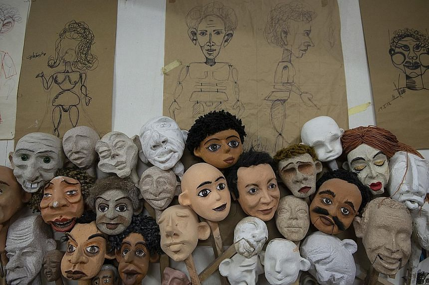 MASTER PUPPETEER: Mr Mohamed Fawzy Bakkar works on a puppet in his Cairo workshop. The 34-year-old has been in the puppet-making business for 15 years and dreams of touring the world with his puppets. MANY EXPRESSIONS: Drawings and faces of puppets l