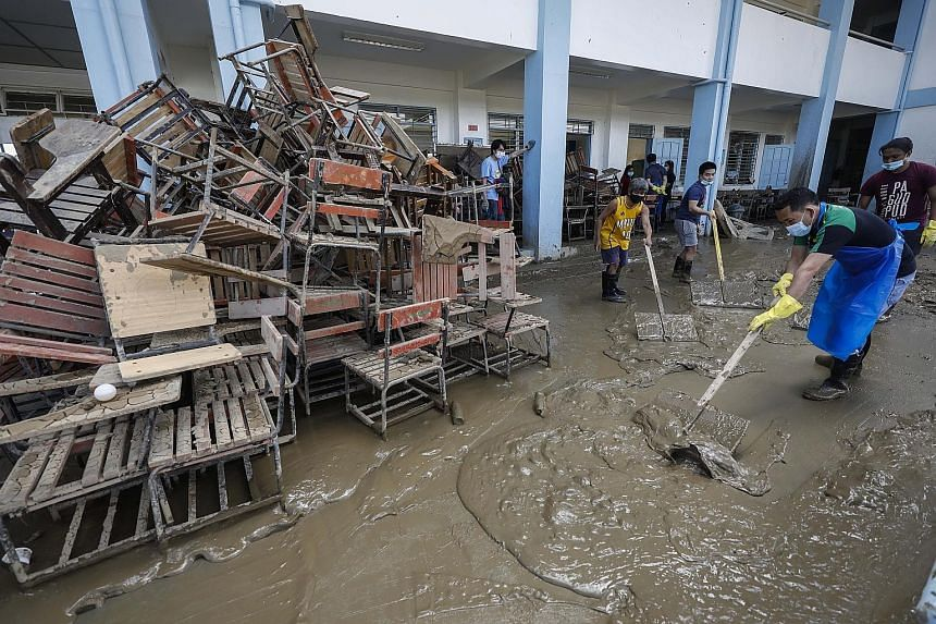 Residents and staff of a school at a riverside community in Marikina City, Metro Manila, cleaning up damage from the storm last week. Typhoon season has been especially active in the Philippines this year.