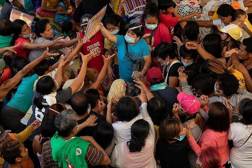 Residents affected by Typhoon Vamco crowding around a group giving away sleeping mats in an evacuation centre in Rodriguez, Rizal province, last Friday. The country's National Disaster Risk Reduction and Management Council said nearly 140,000 people