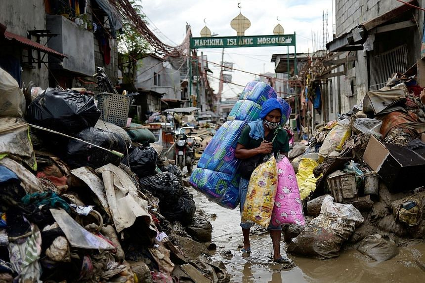A man selling pillows and mattresses walking past debris from the flood brought by Typhoon Vamco, in Marikina City, Metro Manila, last Monday. It is estimated the typhoon caused $242 million in damage to infrastructure.