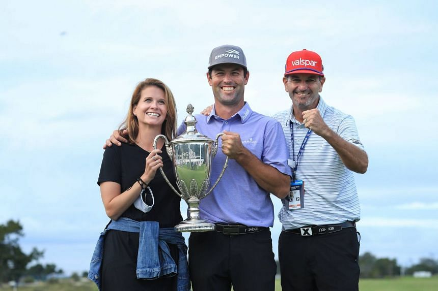 Streb (centre) celebrates winning the trophy with wife Maggie and caddie Steve Catlin.