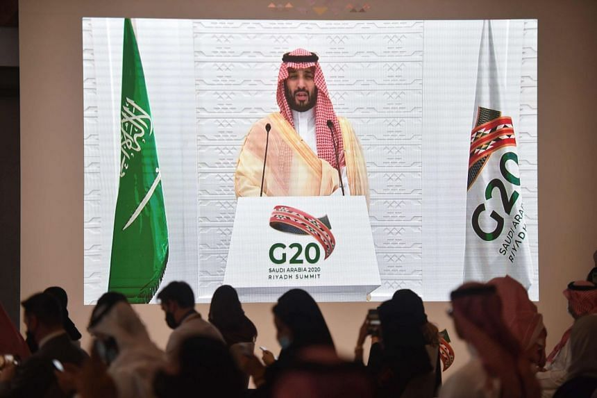 Media representatives listen as Saudi Crown Prince Mohammed bin Salman remotely addresses a press conference at the G20 summit's media centre.