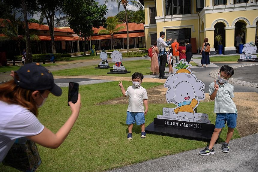 Ms Jermaine Chua, 33, snapping a picture of her sons - four-year-old Tate and seven-year-old Ian - as they posed with a standee of Ai on the front lawn of the Malay Heritage Centre last Friday. The mascot created by artist Peter Draw is at the centre
