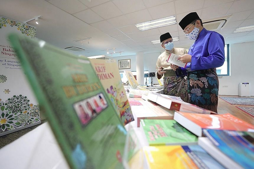 Second Minister for Education Maliki Osman (right) and Malay Language Centre of Singapore centre director Mohamed Noh Daipi looking at teaching resources at the centre yesterday as it celebrated its 10th year. ST PHOTO: GAVIN FOO
